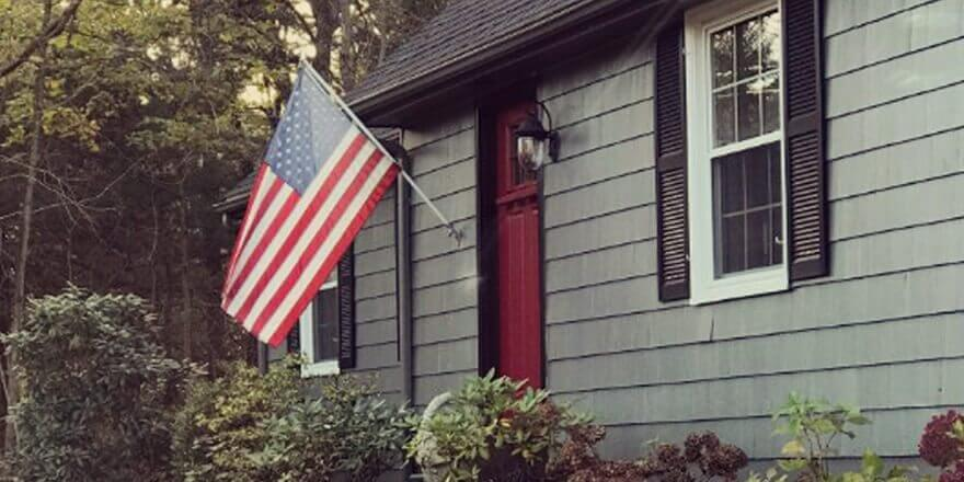 A gray home with an American flag flying in front.